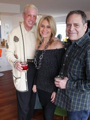 Interior designer Jamie Gibbs, left, poses with a cocktail and Jenny Bizzoco and Hector Rosa inside the Tarkington Tower condominium he helped design.