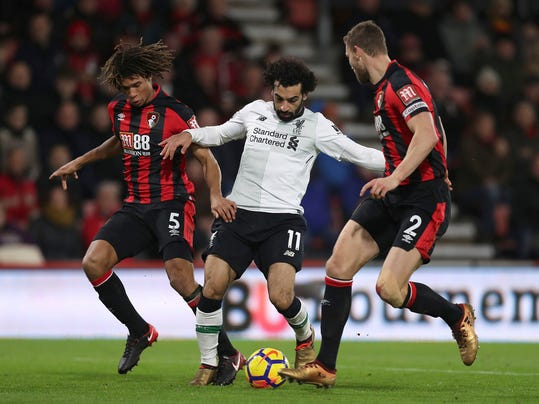 Liverpool's Mohamed Salah, centre, battles with AFC Bournemouth's Nathan Ake, left, and Simon Francis during  during the English Premier League soccer match at the Vitality Stadium in Bournemouth, England, Sunday Dec. 17, 2017. (Andrew Matthews/PA via AP)