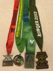 Finisher medals for, from left, the XTERRA World Championships, the Guam Ko'ko' Half Marathon, the Tour of Guam and Konqer, all earned by Blanda Camacho during November 2015.