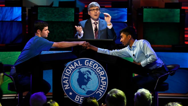 Host Mo Rocca applauds at center as Thomas Wright, 14, of Mequon (left) congratulates Pranay Varada, 14, of Carrollton, Texas, on winning the 2017 National Geographic Bee on Wednesday in Washington, D.C.