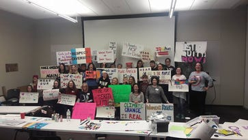 Women's March participants hold signs during a meeting. About 700 Iowans will march in Washington, D.C., and about 3,000 will march at the Iowa Capitol on Saturday, Jan. 21, the day after Donald Trump is sworn in as the 45th president of the United States.