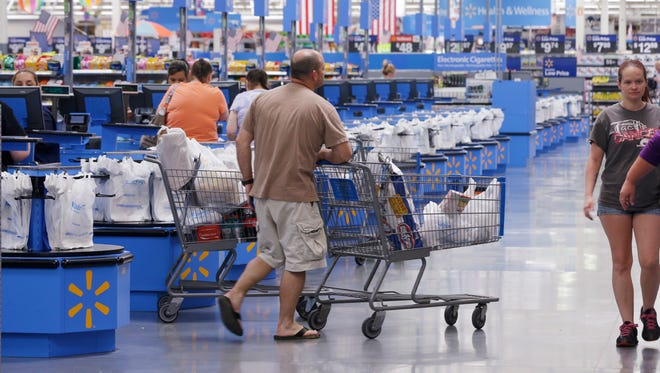 Shoppers walk from the checkout at a Walmart Supercenter store in Springdale, Ark., Thursday, June 4, 2015.