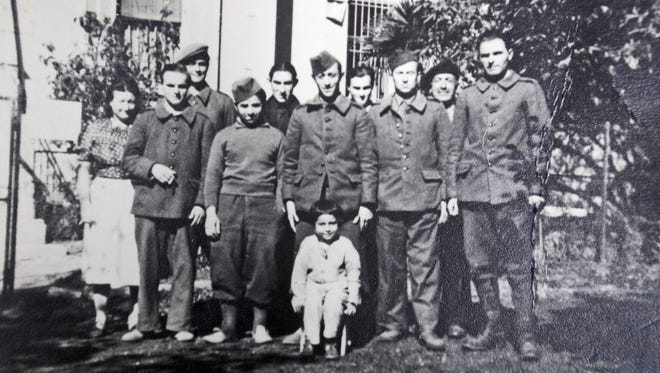 A photograph of Holocaust survivor Helga Luden, of New Rochelle, as a six-year old, with the group of French partisans who found her after she crawled under a barbed wire fence and escaped a Nazi concentration camp in France by herself. Leden was eventually reunited with her parents, who both survived concentration camps.
