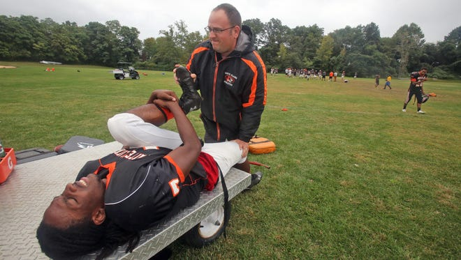 White Plains High School football player Eddie Thomas has his leg stretched by athletic trainer Mike Mirabella during practice on Sept. 29, 2015.