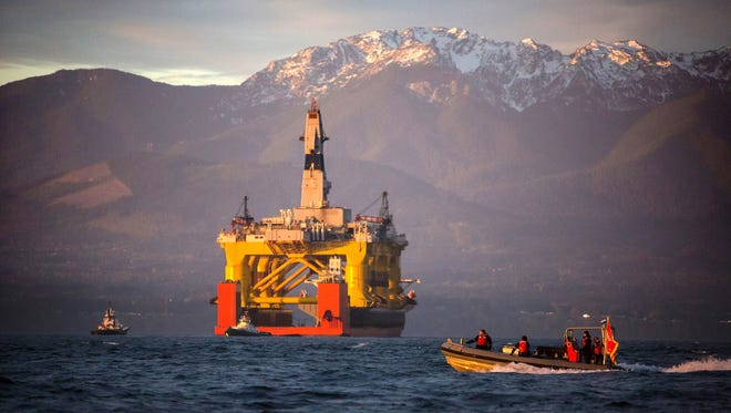 In this April 17, 2015 file photo, a small boat crosses in front of the Transocean Polar Pioneer, a semi-submersible drilling unit that Royal Dutch Shell leases from Transocean Ltd., as it arrives in Port Angeles, Wash. aboard a transport ship after traveling across the Pacific before its eventual Arctic destination. The Interior Department announced Friday, Oct. 16,  it is canceling future lease sales and will not extended current leases in Arctic waters off Alaska's northern coast, a decision that significantly reduces the chances for future Arctic offshore drilling.