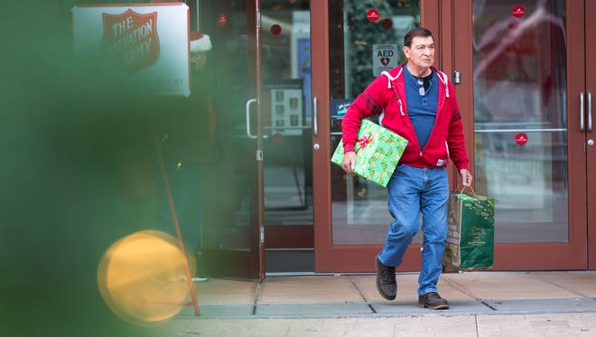 John Ventura of Fairport walks out of Eastview Mall carrying presents after holiday shopping for his wife on Dec. 18, 2015.