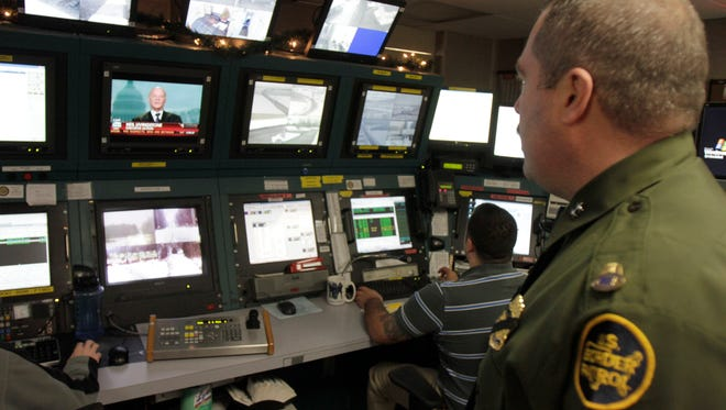 A Border Patrol agent looks over security screens in the command center in Swanton.