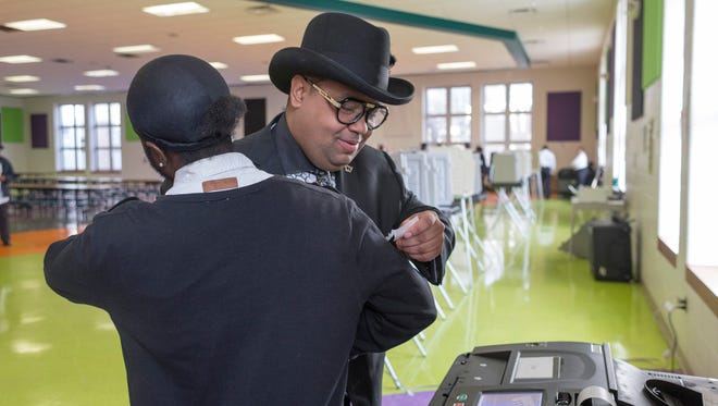 Coleman A. Young II, right, finishes voting and thanks poll worker, Akeem Howard, of Detroit, at the Butzel Family Recreation Center on Tuesday, Nov. 7, 2017 in Detroit.