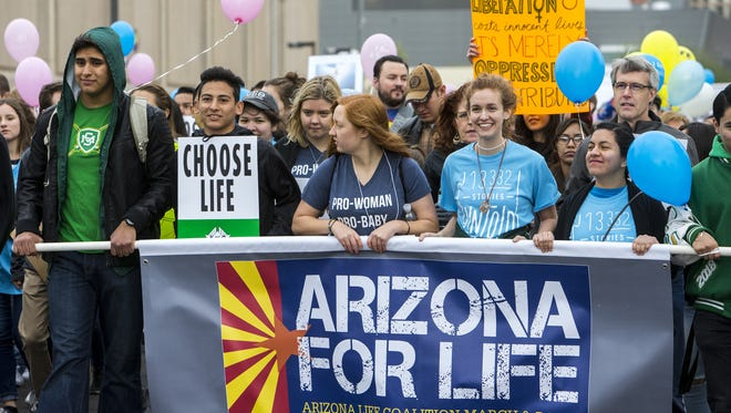 Demonstrators walk down Washington Street in Phoenix during the Arizona for Life March and Rally on Jan. 20, 2018.
