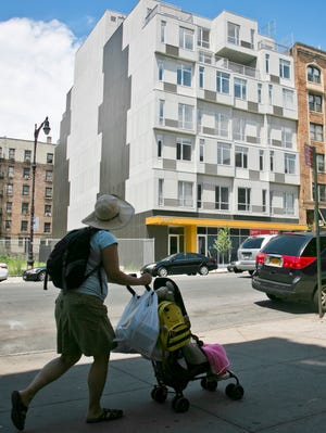 A seven-story modern modular apartment building called the Stack, center, is shown next to a decades-old residence on July 9 in the Innwood neighborhood of New York. The Stack's 28 apartments were formed from 59 modules of rectangular components all 12.5 feet wide and 50 to 60 feet long. It's billed as the first multistory, modular-built apartment building to open in the city.