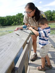 A naturalist and child participate in an activity called