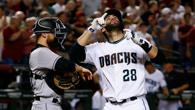 Arizona Diamondbacks' J.D. Martinez (28) points to the sky as he arrives at home plate in front of Colorado Rockies' Jonathan Lucroy, left, after Martinez connected for a home run during the second inning of a baseball game Tuesday, Sept. 12, 2017, in Phoenix.