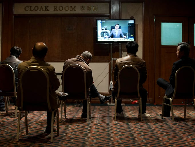 Relatives of Chinese passengers aboard the missing Malaysia Airlines jet watch a television news program about the aircraft at a hotel ballroom on March 20 in Beijing. The Boeing 777 jetliner with 239 people on board vanished on March 8 on a flight from Kuala Lumpur to Beijing.