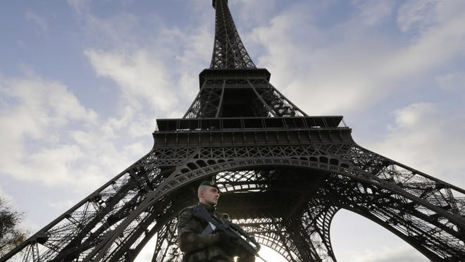 A French soldier stands alert at the Eiffel Tower as it remained closed Sunday – the first of three days of national mourning. The death toll from Friday's attacks in Paris stands at 129.