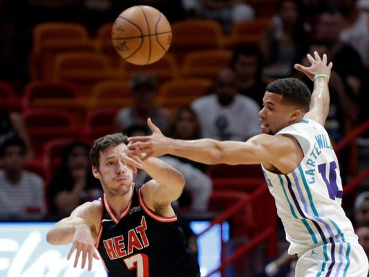 Miami Heat's Goran Dragic (7) passes as Charlotte Hornets' Michael Kidd-Gilchrist (14) defends during the first half of an NBA basketball game, Friday, Dec. 1, 2017, in Miami. (AP Photo/Lynne Sladky)