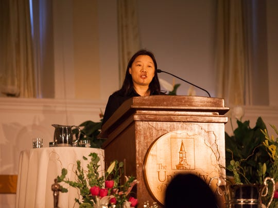 "Guohong Xu of Beihang University in China speaks Friday at the memorial service for Alfred ""Tuna"" Snider. She invited Snider to China to teach debating to  her students."