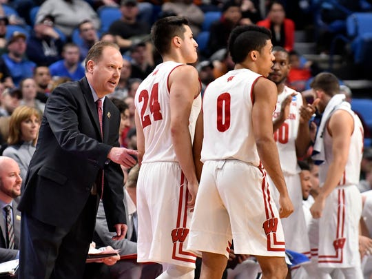 Badgers head coach Greg Gard talks with guard Bronson Koenig (24) and guard D'Mitrik Trice (0) during a time out against the Virginia Tech Hokies in the second half during the first round of the NCAA Tournament at KeyBank Center in Buffalo.