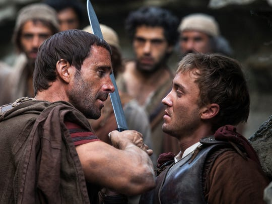"lavius (Joseph Fiennes, left) warns Lucius (Tom Felton) to let them all pass, after he discovers him leading the apostles away from the Roman soldiers in a scene from ""Risen."""