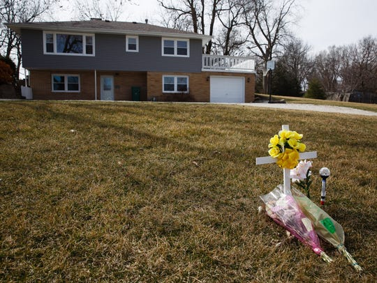 A memorial stands outside the Sharp family home on