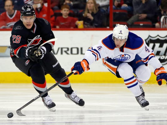 Edmonton Oilers' Taylor Hall (4) poke the puck away from Carolina Hurricanes' Alexander Semin (28), of Russia, during the second period of an NHL hockey game in Raleigh, N.C., Sunday, March 16, 2014. (AP Photo/Karl B DeBlaker)