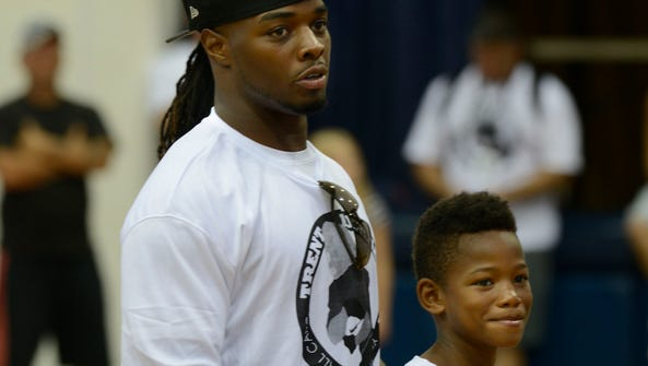 Trent Richardson of the Oakland Raiders, gives kids