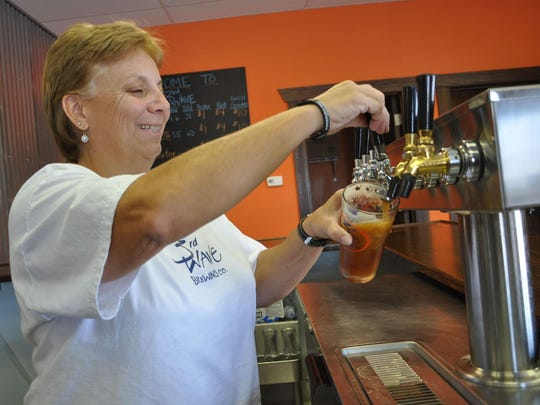 Co-owner and brewery manager Lori Clough pours a beer at 3rd Wave Brewing Co.