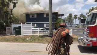 A Fort Myers firefighter lays down hoses at a house fire in the 3000 block of East Riverside Drive in Fort Myers on Wednesday.