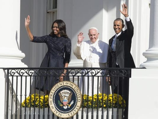 First lady Michelle Obama, Pope Francis and President Obama wave from the balcony of the South Portico after an arrival ceremony at the White House on Sept. 23, 2015.