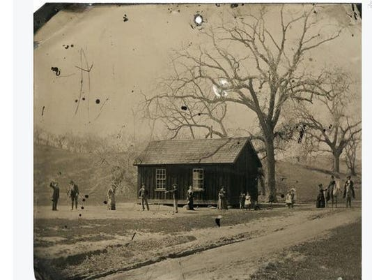 """The 4x5 """"tintype"""" shows the outlaw and members of his gang playing croquet near a small cabin."""