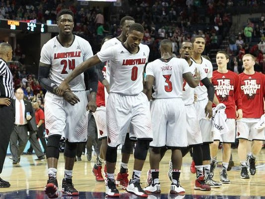 Louisville players Montrezl Harrell (24) and guard Terry Rozier (0) walk off the court at halftime of a game against Connecticut.