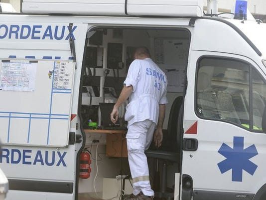 A doctor coordinates help from an ambulance following the fatal bus crash in Puisseguin, near Bordeaux, France, on Oct. 23.