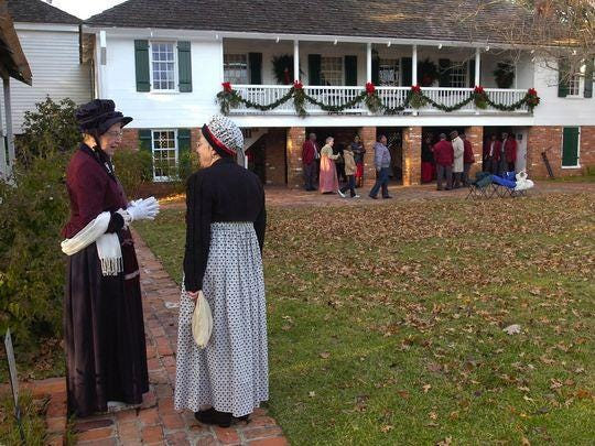 Ann Bice (left) and Margie McBride, volunteers at the Kent Plantation House, are dressed in clothing from the early 1800s, as they take part in the 2008 Old-Fashion Christmas at the historical plantation house.