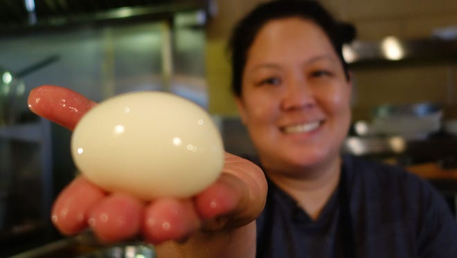 Chef Lori Hashimoto holds a peeled hard-boiled egg before she preps it into her restaurant's signature dish-The Hana fried egg.
