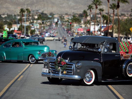 Cars with the Street Kingz Valle de Coachella participate in the Desert Hot Springs Holiday Parade on Saturday.