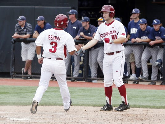 Arkansas's Michael Bernal (3), a Hanks High School graduate, is congratulated by Joe Serrano (10) after Bernal scored off a single by Tucker Pennell against Oral Roberts in the third inning of a game at the Stillwater Regional of the NCAA college baseball tournament in Stillwater, Okla., Friday, May 29, 2015. (AP Photo/Sue Ogrocki)