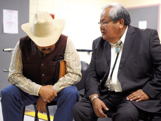 From left, former Navajo Nation Council speaker Lawrence T. Morgan and current speaker Johnny Naize wait on March 11 for an arraignment hearing outside the courtroom at Window Rock District Court in Window Rock, Ariz. Both men are accused of misusing the tribal council's discretionary fund.