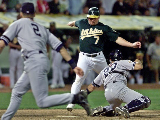 ORG XMIT: OAS115 Oakland Athletics' Jeremy Giambi, center, is tagged out at home by New York Yankees' Jorge Posada, right, during Game 3 of the American League Division Series, in Oakland, Calif., Saturday, Oct. 13, 2001.  Giambi tried to score from first on a double from Terrence Long in the seventh inning. At left is Yankees short stop Derek Jeter who assisted with a throw from between first and home.  (AP Photo/Eric Risberg) [Via MerlinFTP Drop]