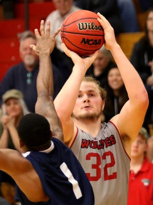 Western Oregon's Andy Avgi (32) shoots a three-pointer past the arm of Western Washington's Ricardo Maxwell (1) in the Western Washington University vs. Western Oregon University men's basketball game at Western Oregon University in Monmouth on Thursday, Feb. 11, 2016. Western Oregon won the game 90-85.
