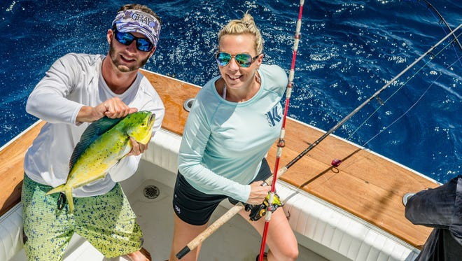 Luke Grogis and Crystal Pion display one of many mahi caught during a fishing excursion on the Reel Candy.