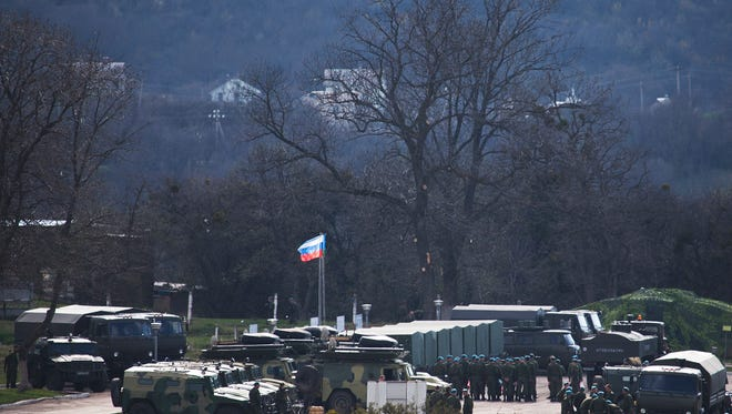 A Russian national flag flies over Russian troops as they gather at a former Ukrainian military base in Perevalne, outside Simferopol, Crimea.