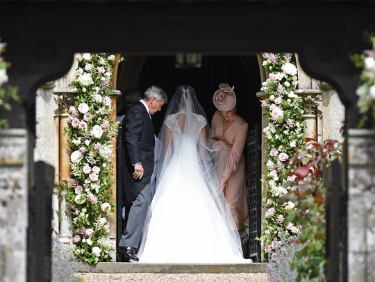 Duchess Kate of Cambridge (R), adjusts the dress of