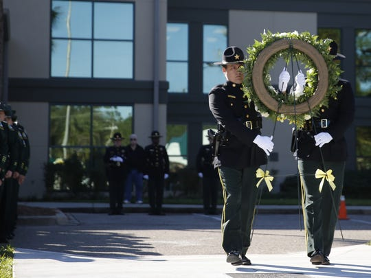 Leon County Sheriff Officers carry a flower wreath during a memorial ceremony for fallen officers at the LCSO Office on Friday.