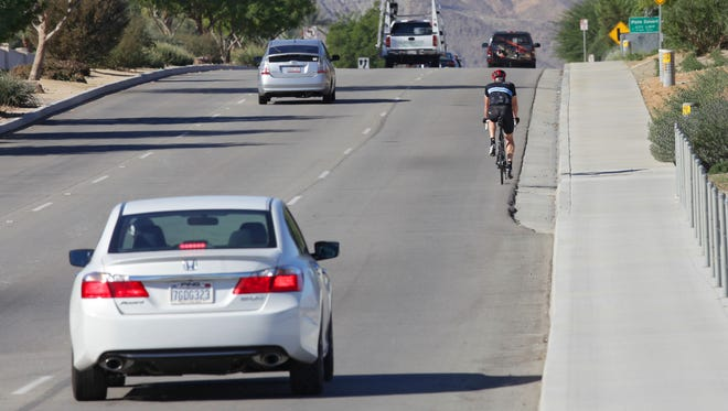A motorist applies the brakes after a cyclist is forced into traffic in this file photo of Fred Waring Drive near the Indian Wells and Palm Desert. On Wednesday morning, a mother and son on a tandem bike in Cathedral City were struck and injured while biking to the boy's school.