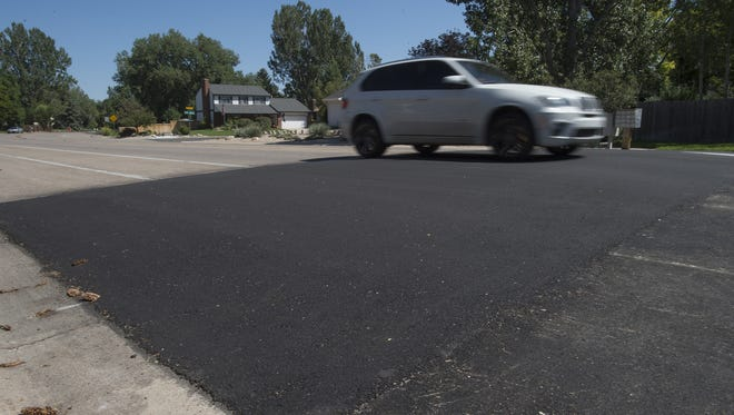 A driver heads west on Swallow Road over a new speed hump.