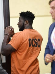 Cory Batey signals his family after being sentenced