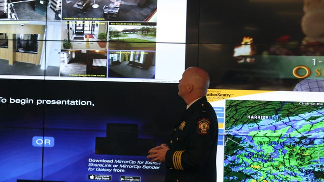 Emergency Communication Chief Jeffrey P. Miller explains how the surveillance monitor in the upper-left corner functions at New Castle County's J. William Bell Fusion Center.