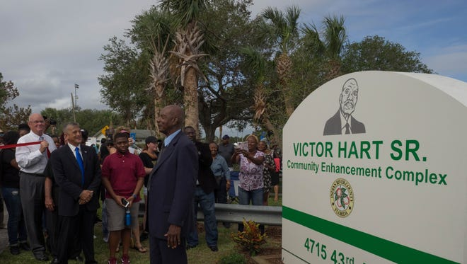 Victor Hart Sr. stands in front of the sign bearing his name, after its unveiling by County Commissioners Bob Solari and Joe Flescher, at left.