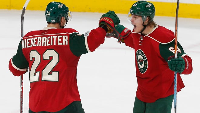 Minnesota Wild's Mikael Granlund, right, of Finland, celebrates the go-ahead goal by Nino Niederreiter, left, of Switzerland off Arizona Coyotes goalie Louis Domingue during the third period of an NHL hockey game Thursday, Jan. 19, in St. Paul. The Wild won 4-3. Niedereitter scored two goals in the game.