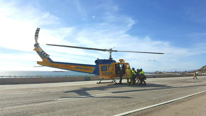A patient is loaded into a helicopter after being thrown from a vehicle along northbound 101 near La Conchita on Monday.