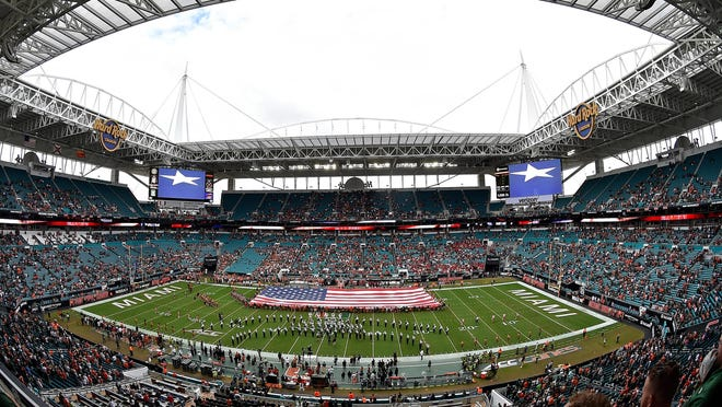 An American flag is displayed during the national anthem prior to a game between the Louisville Cardinals and Miami Hurricanes at Hard Rock Stadium.